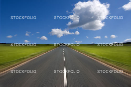 Rural road stretching out into the distance with motion blur under a big expanse of blue sky