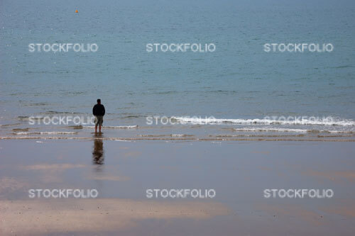 Solitary man wearing shorts standing on the edge of a beach looking out to sea