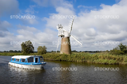 A boat passing Turf Fen windpump on the River Ant, Norfolk Broads
