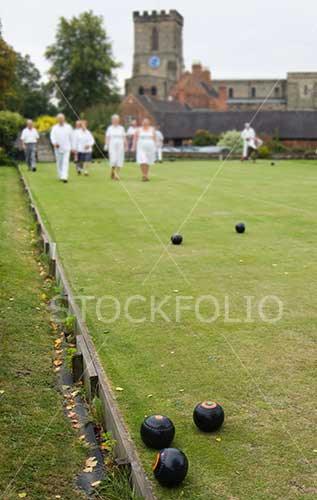 People playing crown green bowls in a English village