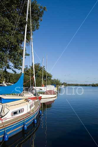 Yachts moored on a blue lake