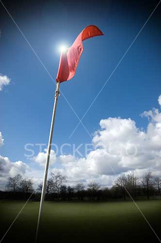 Red flag on a gold course fluttering in the wind
