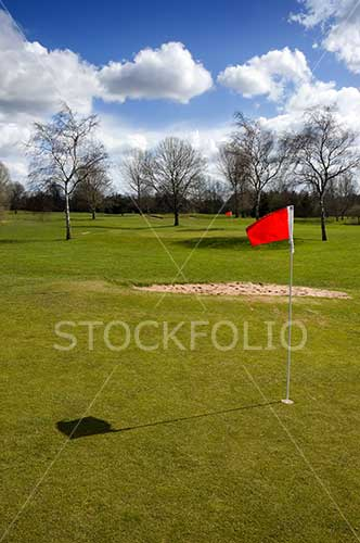 Red flag and bunker on the green of a gold course