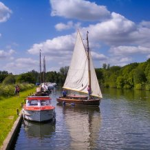 A yacht leaving it's moorings on Fleet Dyke on the Norfolk Broads